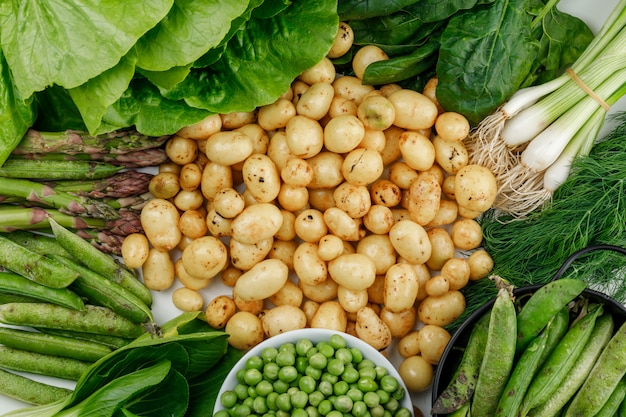 Potatoes with green pods, peas, dill, green onions, spinach, sorrel, lettuce, asparagus flat lay on a white wall