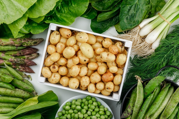 Potatoes with green pods, peas, dill, green onions, spinach, sorrel, lettuce, asparagus in a wooden box on white wall, top view.