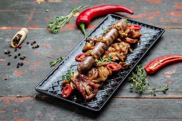 Картофель с сосисками, нарезанный кружочками и обжаренный в масле, подается с перцем чили и горчицей