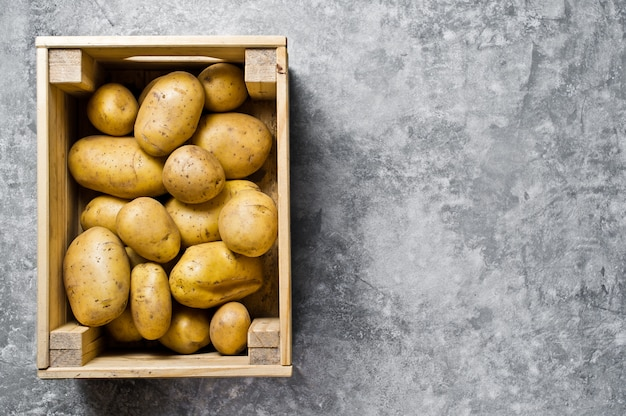 Potatoes in a wooden box, supermarket.