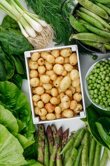 Potatoes in a wooden box with green pods, peas, dill, green onions, spinach, sorrel, lettuce, asparagus top view on a white wall