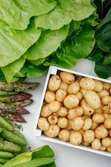 Potatoes in a wooden box with green pods, spinach, sorrel, lettuce, asparagus flat lay on a white wall