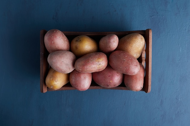 Potatoes in a wooden tray, top view.