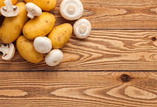 木製の背景にジャガイモとキノコ