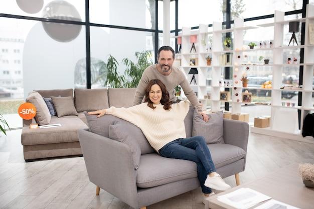 Потенциальные покупатели в мебельном салоне выглядят счастливыми и довольными.