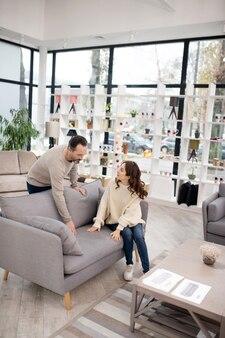 Потенциальные покупатели пробуют и проверяют новый диван