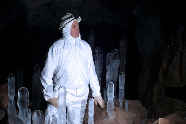 어두운 배경의 동굴에 있는 얼음 석순 사이에 흰색 작업복을 입은 구덩이