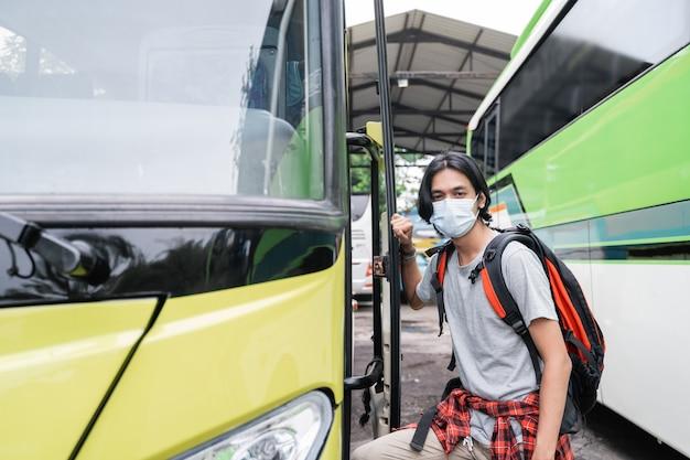 버스에 점점 얼굴 마스크를 쓰고 potrait 아시아 젊은 남자. 얼굴 마스크를 쓰고 배낭을 들고 남자는 터미널에서 버스에 도착