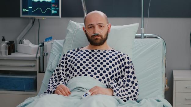 Potrait of hospitalized sick man with nasal oxygen tube having respiratory disorder