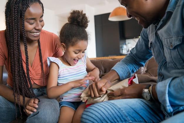 Портрет маленькой девочки удивлен, получив подарок от родителей, оставаясь дома.