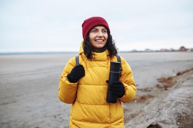 広大な空の冬の谷の低地の間を脇道を歩いているバックパックを持つ若い女性の観光客の肖像画。黄色のジャケットと赤い帽子をかぶった女性旅行者。ヒッチハイク、旅行のコンセプト。