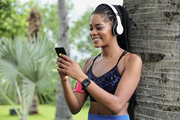 木の幹に寄りかかって、彼女の電話でテキストメッセージを読んでいるかなり笑顔の若いフィット女性の肖像画