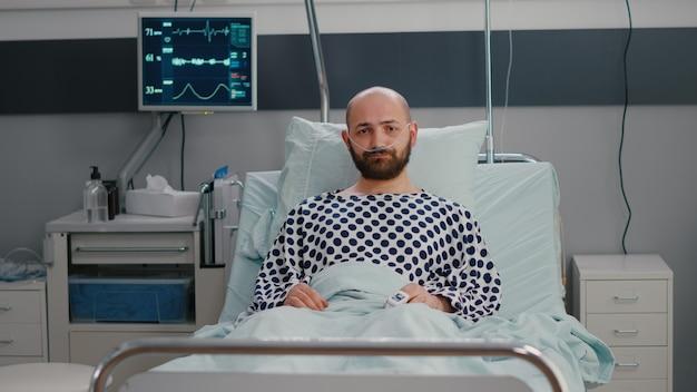 悪い状態で横たわっている鼻酸素チューブを身に着けている悲しい病人のpotrait