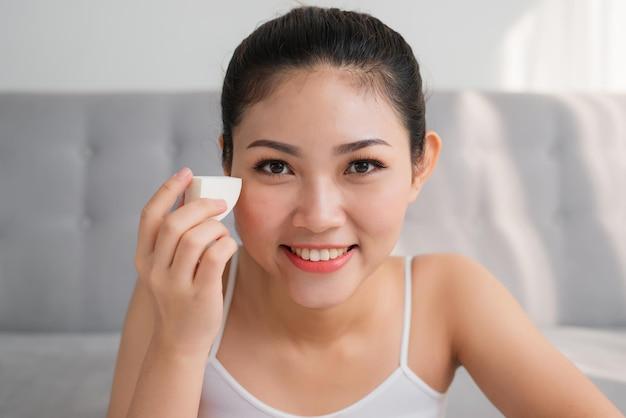 スポンジブレンダーを使用して若いアジアの女性のpotraitは顔にツールを構成します。メイクのコンセプト