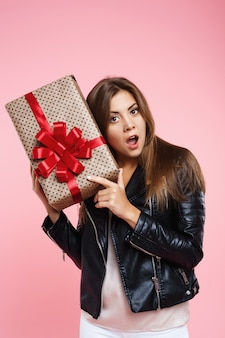 Potrait of surprised girl in trendy look holding present box