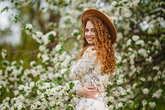 Potrait of a young woman being happy standing among blooming apple trees. a girl enjoys spring and smells white flowers on the trees. season change and fresh day concept.