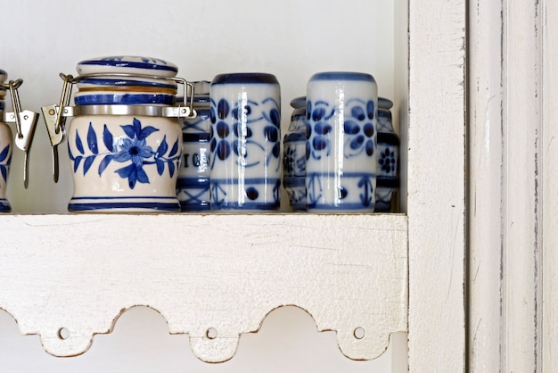Pots of spices in blue porcelain, on white and decorated cabinet shelf