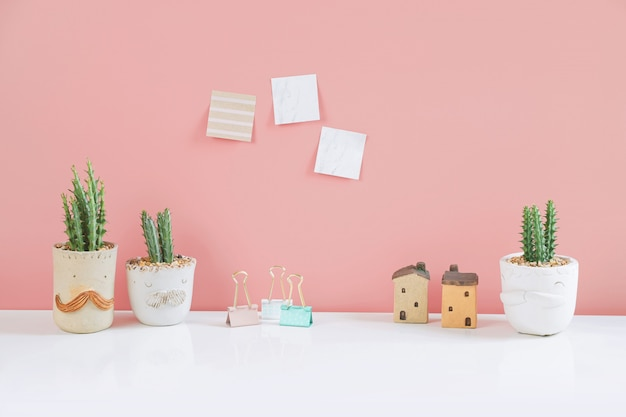 Potted cactus house plants with sticky note on pink wall.