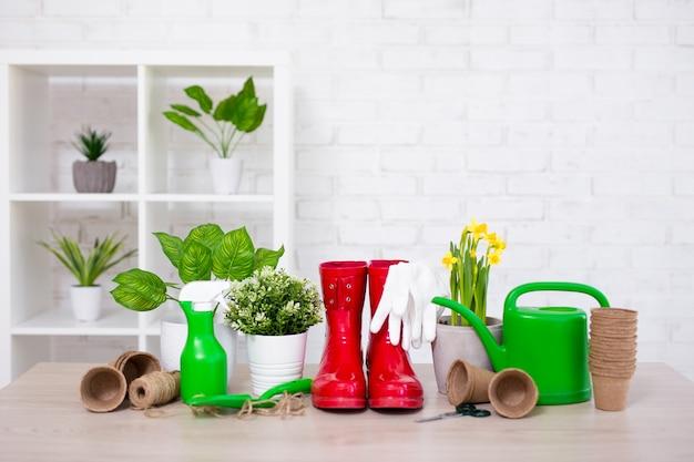白いレンガの壁の上にテキストのためのスペースを持つ鉢植えの花とガーデニングツール