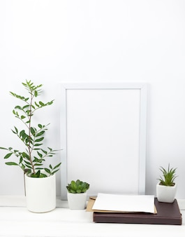 Potted plant; white frame and diary at home