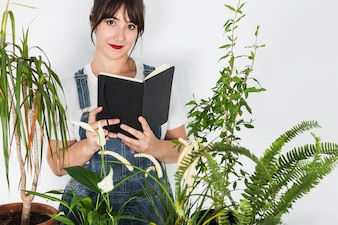 Potted plants in front of beautiful female florist holding diary