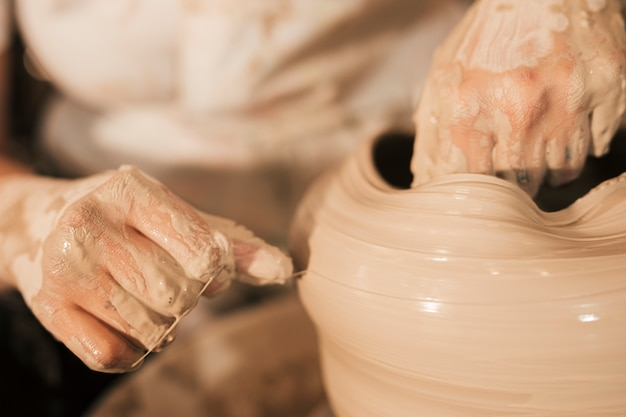 The potter aligns the wet clay pot with thread on the potter's wheel