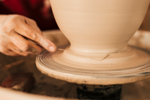Potter cuts the finished clay vase from the spinning wheel