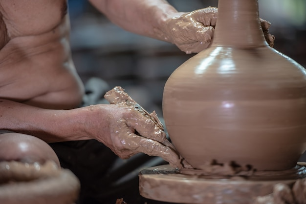 Potter doing pottery on a potter wheel in the factory