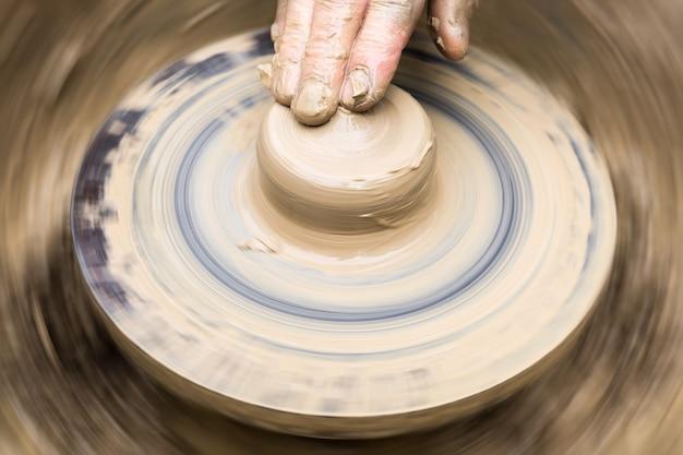 陶芸家の指が回転する車輪の形のない粘土片に触れます