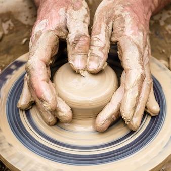 陶芸家の指が糸車の形のない粘土片に触れて形を作ります