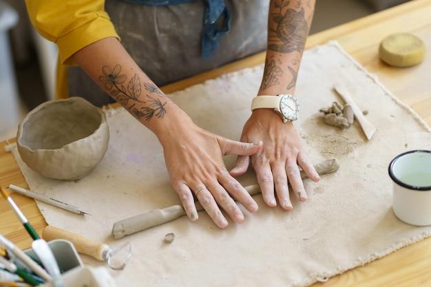 도자기 테이블에 손으로 점토 조각을 굴리는 포터 소녀는 두 팔에 문신이 있습니다