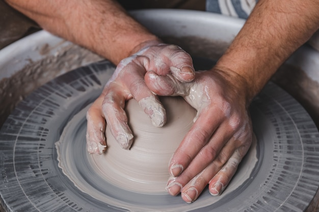 Potter making a new vase of white clay on the potter's wheel circle in studio, concept of manual work, creativity and art, horizontal photo