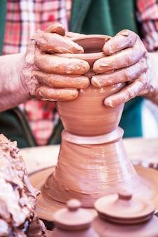 Potter's hand shapes a vessel.