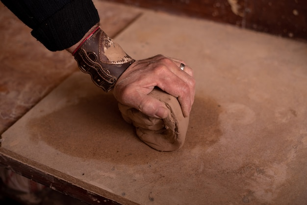 Potter's hands work with clay, making it a product
