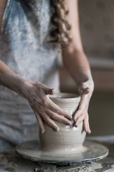 Potter sculpts a vase on a potter's wheel