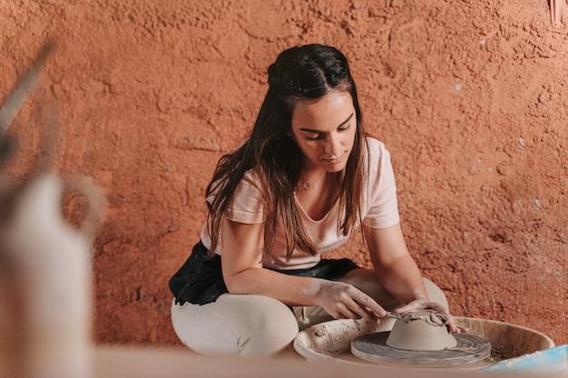 그녀가 만들고있는 꽃병을 물의 도움으로 테라코타라는 재료로 만드는 작업장의 포터 여성