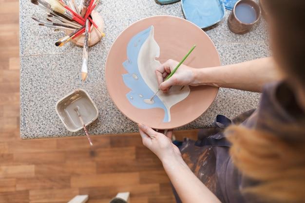 포터 여자는 세라믹 접시를 그립니다.