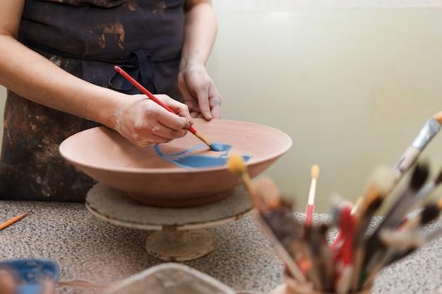 Potter woman paints a ceramic plate.