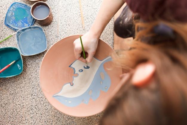 Potter woman paints a ceramic plate