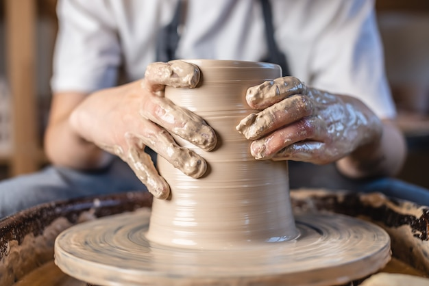 Potter working on a potter's wheel making a vase