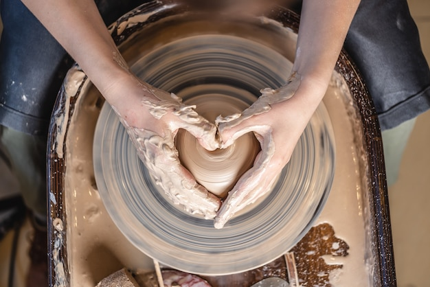 A potter works with clay on a potter's wheel in the workshop. women's hands show a heart sign