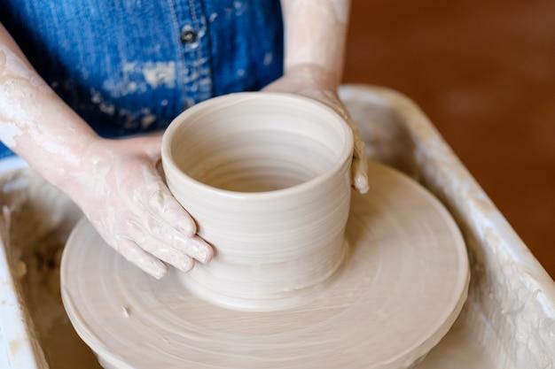 Художественная гончарная терапия. творческий расслабляющий досуг. маленький ребенок руками лепит глиняный кувшин