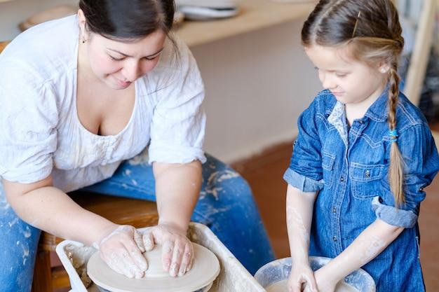 Художественная гончарная терапия. творческий расслабляющий досуг. мастер-гончар учит маленькую девочку лепить глиняный шар