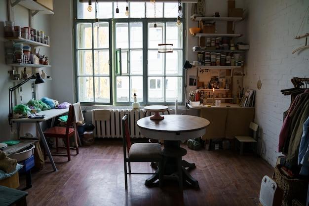 Рабочее место мастерской гончарного искусства, интерьер творческой студии со столом и профессиональным оборудованием.