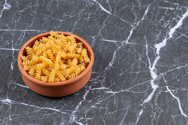 Ciotola di ceramica piena di pasta a spirale cruda.