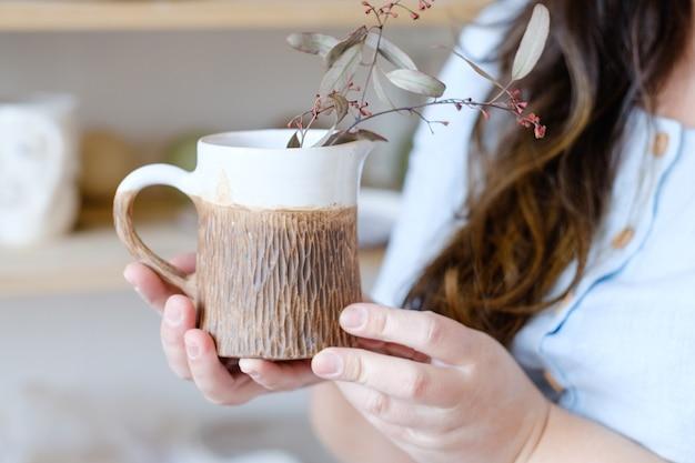 陶芸家。芸術的な趣味や手工芸品の職業。創造的な職業の概念。植物が入ったクラフトクレイマグを持っている手