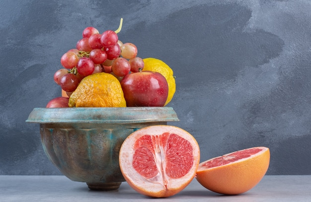 A pottery full of fresh organic fruits. on grey background.