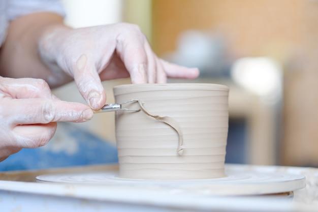 Мастерство гончарного ремесла. традиционное искусство создания керамики. глиняный кувшин для лепки гончара на вращающемся круге