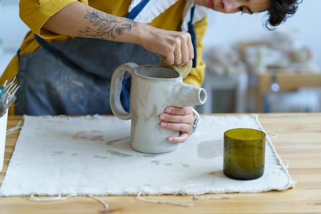 도자기 취미 또는 세라믹 제조 소규모 비즈니스 젊은 예술가가 스튜디오에서 원시 점토 주전자를 성형합니다.