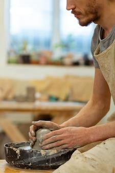 Гончарное мастерство. серьезный бородатый мастер показывает свое мастерство в гончарном деле, работая с гончарным кругом.